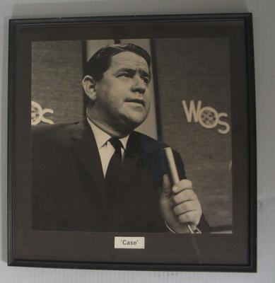 Framed black and white photograph of Ron Casey, holding a microphone; Photography; N2011.58.9