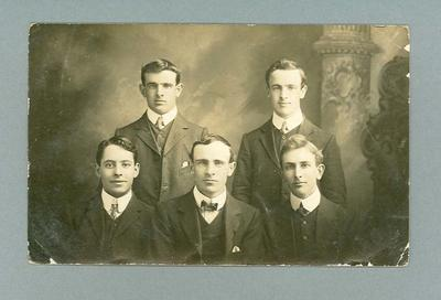 Postcard, depicts five young men in studio setting