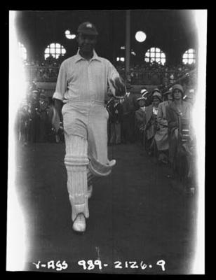 Negative, depicts batsman walking onto a ground c1932