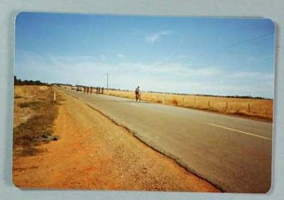 Colour photograph of Eric Gibaud and cyclists riding on Western Highway, 1980s