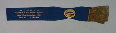 Sash with gold badge attached awarded to Ernie Milliken, VACU Victorian 20 Mile Senior Unpaced Road Championship 1931
