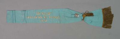 Sash and attached silver badge awarded to Ernie Milliken, Fastest Time, Dunlop Goulburn-Sydney Race 1932