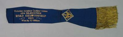 Sash with attached gold and silver badge, awarded to Ernie Milliken, Victorian Amateur Cyclists' Union 62.14 Miles Senior Road Championship 1933
