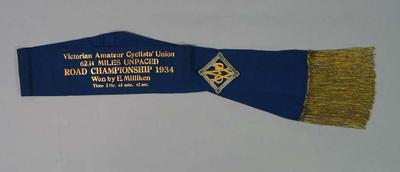 Sash with attached gold and silver brooch, awarded to Ernie Milliken, Victorian Amateur Cyclists' Union 62.14 Miles Unpaced Road Championship 1934
