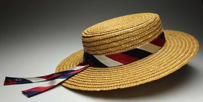Straw boater featuring a hat band fashioned from an MCC tie, created and worn by MCC member Norma Long, circa 2000s