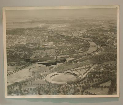 Aerial photograph of MCG with plane flying overhead, c1942