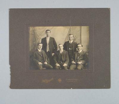Studio photograph of five men in formal attire