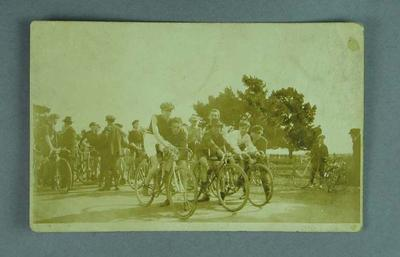 Black and white photograph postcard of a group of cyclists - line-up for a race