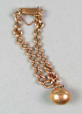 A football-shaped gold charm inscribed J. Byrne 1877, on gold link bracelet
