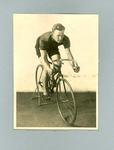 Black and white photograph of L. K. Smith on bicycle