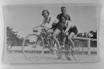 Copy negative of photograph in photo album, depicts tandem cyclists c1930s