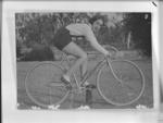 Copy negative of a photograph depicting Dot Edney on a bicycle, c1930s