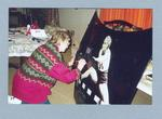 Photograph of Shirley Strickland signing a poster of her hurdling, July 2000