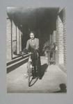 Photograph of Dot Edney [Mansell] standing beside her bicycle in 1936