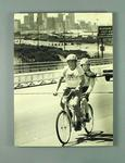 Mounted black and white photograph of Brian Dixon riding a tandem bicycle