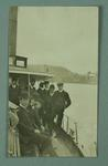 A used black and white photo postcard featuring a number of men posing on a boat sailing around Manly, in Sydney.