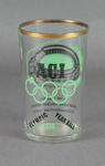 A gold rimmed drinking glass with MCG illustration & ACI Olympic Year Ball 1956