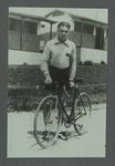Photograph of Dunc Gray with bicycle in front of 1932 Olympic Games team huts, after a training ride