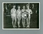 Photograph of four female gymnasts with trophy, c1965