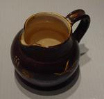 Brown ceramic jug with cricket  bat, pads & ball design and gum leaf motif on sides