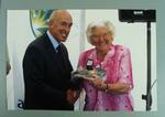 Coloured photograph of Betty Wilson being presented with a baggy green cap and medal by Tony Steele, 25 February 2004.