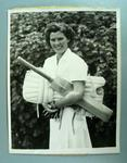Half lenght black and white photograph of Betty Wilson holding her cricket pads and bat - 1948 prior to Test debut.
