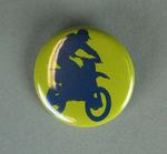 Yellow brooch featuring a silhouette image of a motorbike rider in navy blue