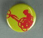 Yellow brooch featuring a silhouette image of a racing wheelchair athlete in red.